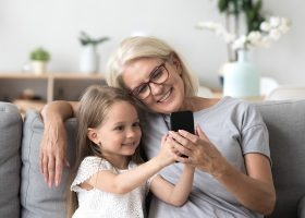 Happy grandmother and cute granddaughter using cellphone making selfie together